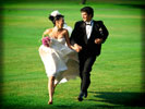 Wedding Couple running in a Green Field